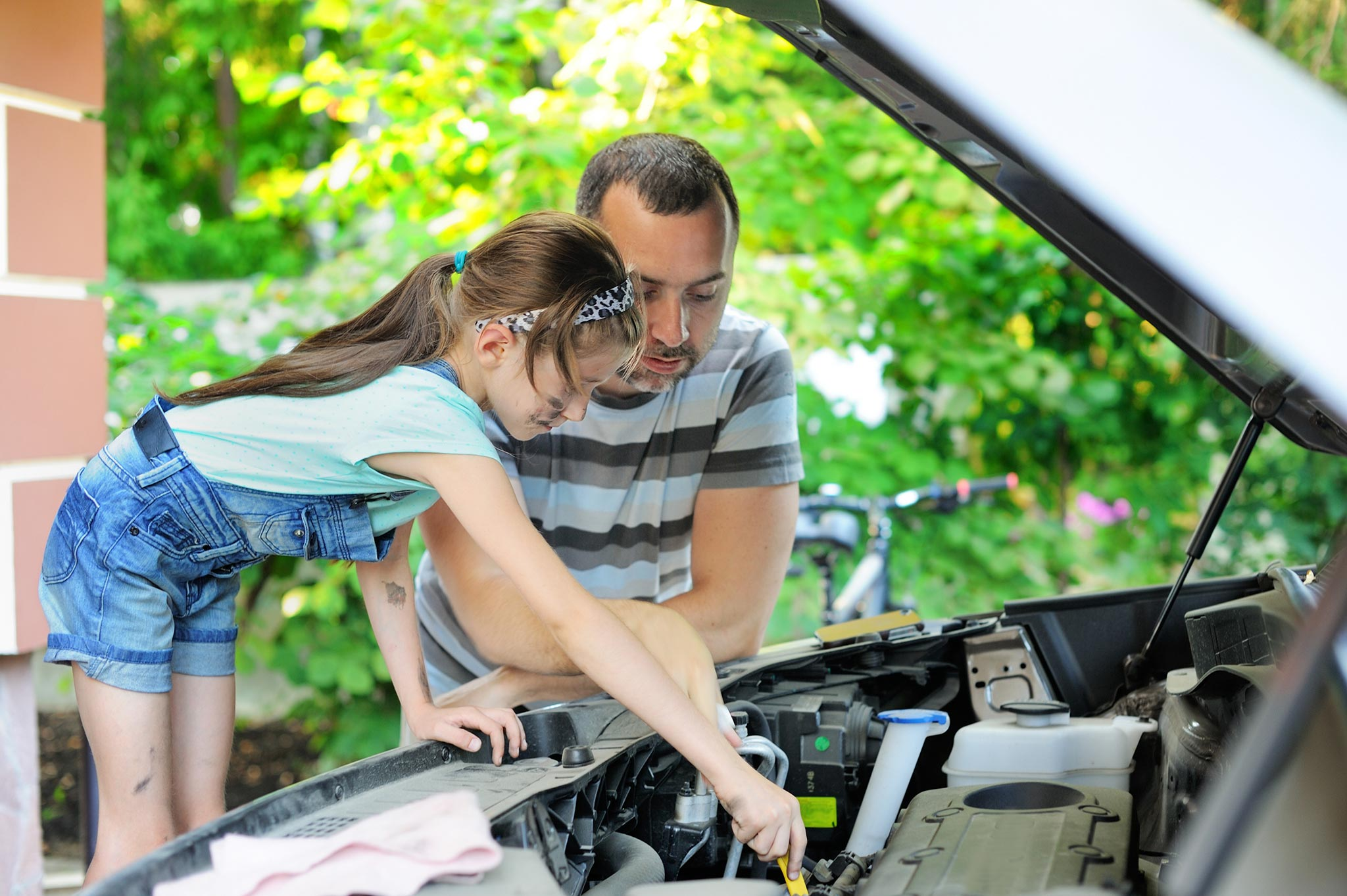 Young girl and father changing car battery